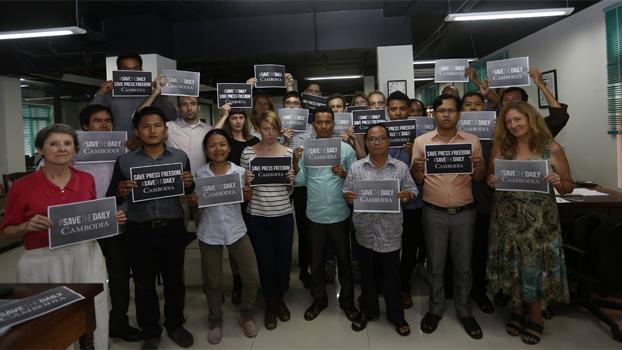 """បុគ្គលិកកាសែត ឌឹ ខេមបូឌា ដេលី (The Cambodia Daily) ក្នុងនេះមានលោក អូន ភាព (នៅជួរមុខពីស្ដាំមកឆ្វេងទី៣) ដែលជាប់បណ្ដឹងពីបទ """"ញុះញង់"""" នៅតុលាការខេត្តរតនគិរី លើកបដាស្វែងរកការជួយសង្គ្រោះកាសែតនេះ កាលពីថ្ងៃទី២៣ ខែសីហា ឆ្នាំ២០១៧។ Photo courtesy of The Cambodia Daily"""
