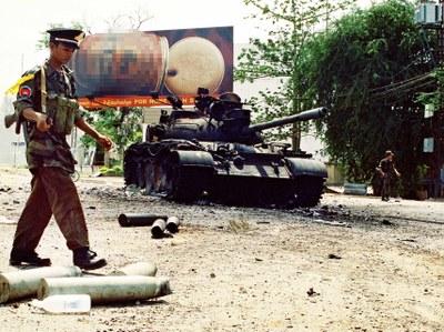 ទាហានរដ្ឋាភិបាលដើរខាងមុខរថក្រោះឆេះនៅលើដងផ្លូវមួយក្នុងរាជធានីភ្នំពេញ កាលពីថ្ងៃ៧ ខែកក្កដា ឆ្នាំ១៩៩៧។ AFP Photo