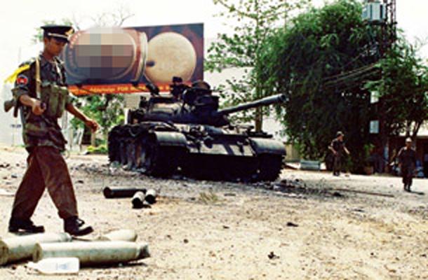 ទាហានរដ្ឋាភិបាលដើរខាងមុខរថក្រោះឆេះ នៅលើដងផ្លូវមួយក្នុងរាជធានីភ្នំពេញ កាលពីថ្ងៃ៧ ខែកក្កដា ឆ្នាំ១៩៩៧។ AFP File Photo