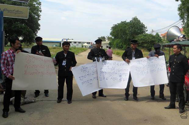 បុគ្គលិកបើកបររថយន្តក្រុមហ៊ុន រ៉ូយ៉ាល់ ខេមបូឌាន លីម៉ូសីន សឺវីស (Royal Cambodian Limousine Service) លើកបដាតវ៉ាមុខច្រកចូលក្រុមហ៊ុន កាលពីព្រឹកថ្ងៃទី២៧ ខែកក្កដា ឆ្នាំ២០១៥។ RFA/Sek Bandith